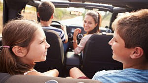 Photo of a family laughing together in a car